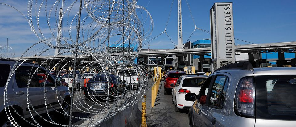 Concertina wire is shown as vehicles enter the United States from Mexico as authorities prepare for the arrival of a caravan of migrants at the San Ysidro border crossing in San Diego
