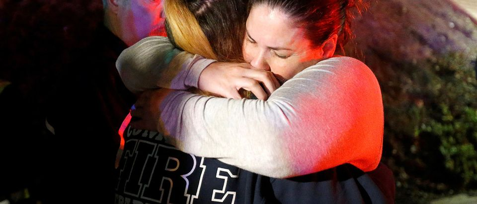 People comfort each other after a mass shooting at a bar in Thousand Oaks