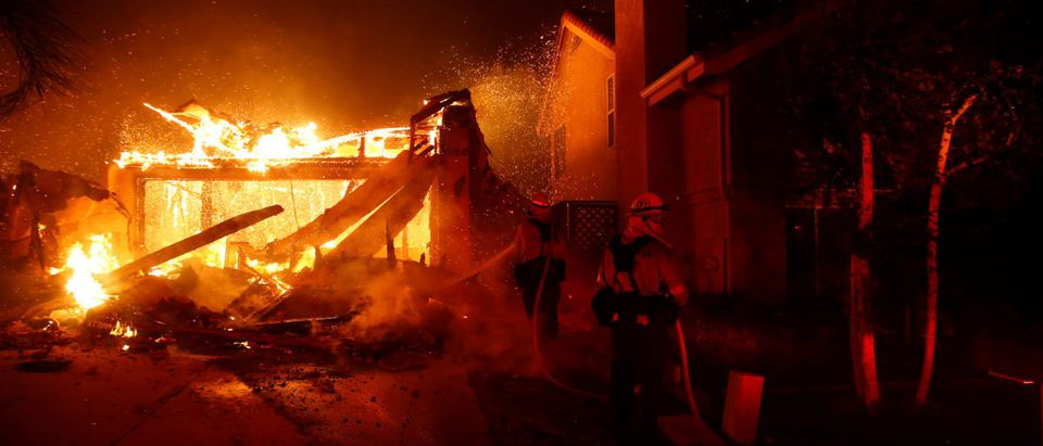 Firefighters battle flames overnight during a wildfire that burned dozens of homes in Thousand Oaks, California, U.S. Nov. 9, 2018. REUTERS/Eric Thayer