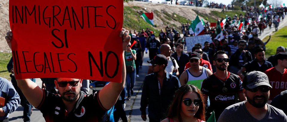 "A demonstrator holding a placard that reads, ""Immigrants yes, illegals not"" attends to a protest against migrants who are part of a caravan traveling en route to the United States, in Tijuana"