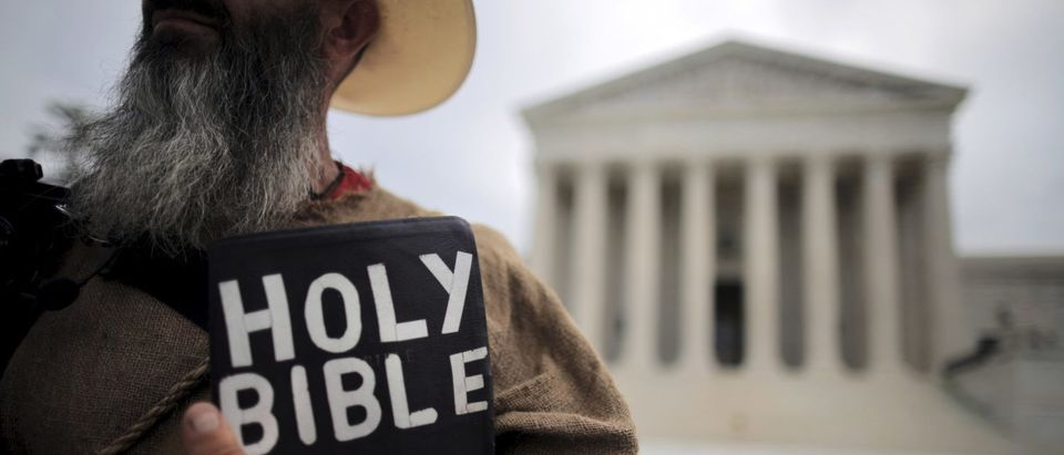 A protester holds a copy of the Bible outside of the U.S. Supreme Court building in Washington June 15, 2015. REUTERS/Carlos Barria