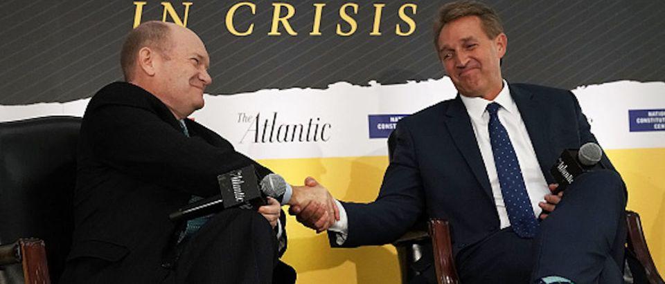 U.S. Sen. Chris Coons (D-DE) (L) and Sen. Jeff Flake (R-AZ) (R) shake hands during a discussion at the 2018 Atlantic Festival October 2, 2018 in Washington, DC