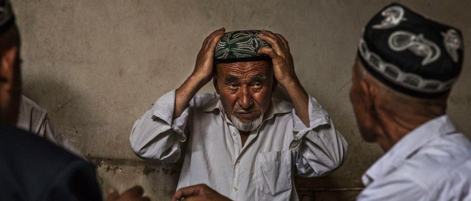 KASHGAR, CHINA - JULY 1: An ethnic Uyghur man adjust his traditional hat called a doppa as he talks with others at a teahouse on July 1, 2017 in the old town of Kashgar, in the far western Xinjiang province, China. (Photo by Kevin Frayer/Getty Images)