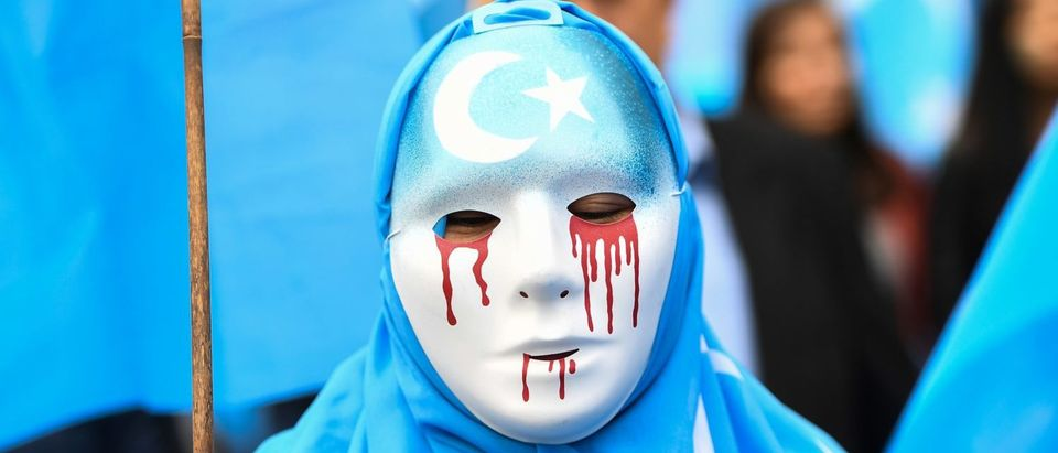 "A person wearing a white mask with tears of blood takes part in a protest march of ethnic Uighurs asking for the European Union to call upon China to respect human rights in the Chinese Xinjiang region and ask for the closure of ""re-education center"" where Uighurs are detained, during a demonstration around the EU institutions in Brussels on April 27, 2018. (EMMANUEL DUNAND/AFP/Getty Images)"