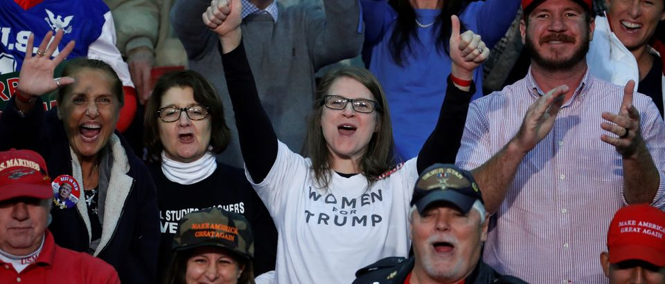 """People including a woman wearing a """"Women for Trump"""" shirt cheer for U.S. President Donald Trump as he speaks at a rally in Pensacola, Florida"""