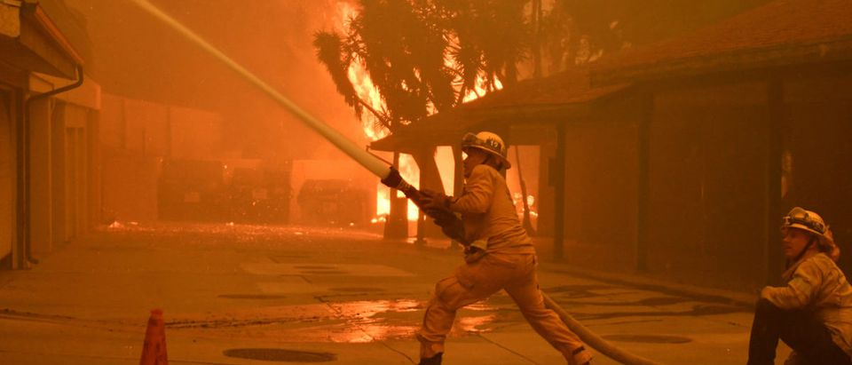 Firefighters hose down a condo unit during the Woolsey Fire in Malibu, California, U.S. November 9, 2018. REUTERS/Gene Blevins