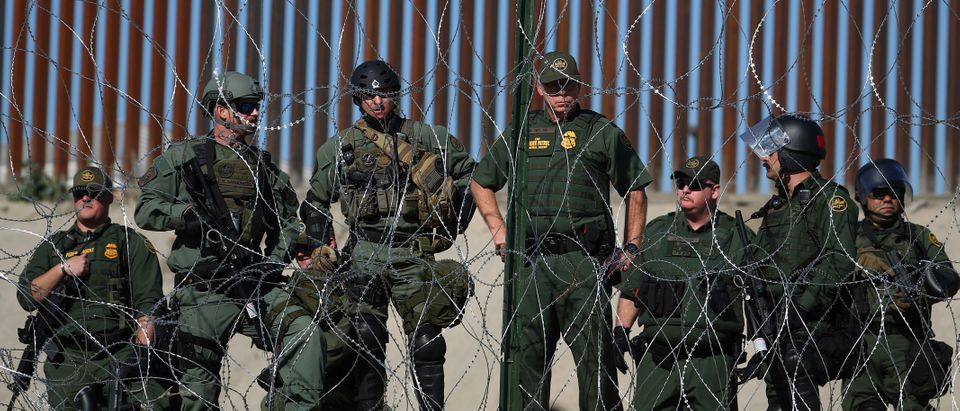 U.S border patrol stand near the border fence between Mexico and the United States as migrants stand near by in Tijuana