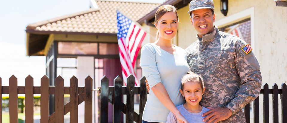 A military family stands outside their home. Shutterstock image via user michaeljung