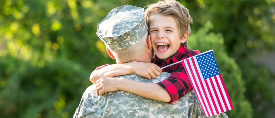 A boy hugs his father. Shutterstock image via user Peppersmint