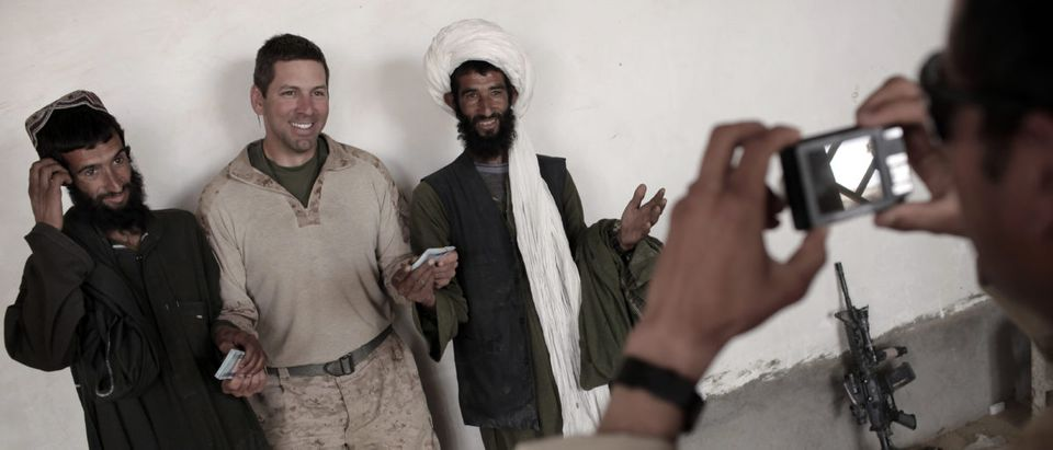An interpreter for U.S. Marines of India Company, 3rd Battalion, 6th Marines takes a souvenir picture requested by the U.S. officer giving 20,000 Afghanis each to two brothers for damages to their residences caused during the ongoing U.S. military offensive against Taliban insurgency, in Marjah, Helmand province, southern Afghanistan, on April 12, 2010. (MAURICIO LIMA/AFP/Getty Images)