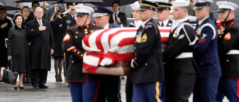 Former President George W. Bush and Laura Bush watch as the flag-draped casket of former President George H.W. Bush is carried by a joint services military honor guard to a Union Pacific train on December 6, 2018 in Houston, Texas. President Bush will be buried at his final resting place at the George H.W. Bush Presidential Library at Texas A&M University in College Station, Texas. A WWII combat veteran, Bush served as a member of Congress from Texas, ambassador to the United Nations, director of the CIA, vice president and 41st president of the United States. (Photo by David J. Phillip-Pool/Getty Images)