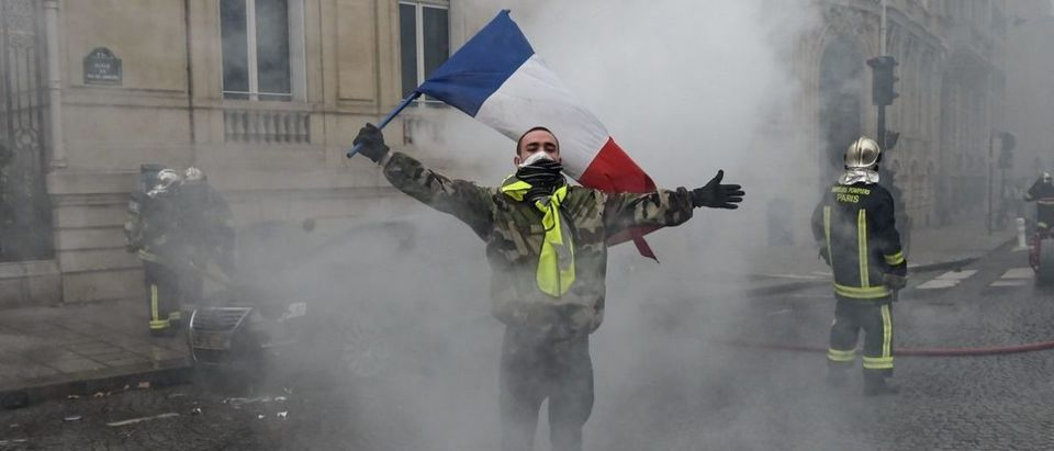 "A protestor waves a French flag amid smoke during clash with riot police near the Champs Elysees in Paris on December 8, 2018 during a ""yellow vest"" (gilet jaune) protest against rising costs of living they blame on high taxes. - Paris was on high alert on December 8 with major security measures in place ahead of fresh ""yellow vest"" protests which authorities fear could turn violent for a second weekend in a row. (Photo by Lucas BARIOULET / AFP) (Photo credit should read LUCAS BARIOULET/AFP/Getty Images)"