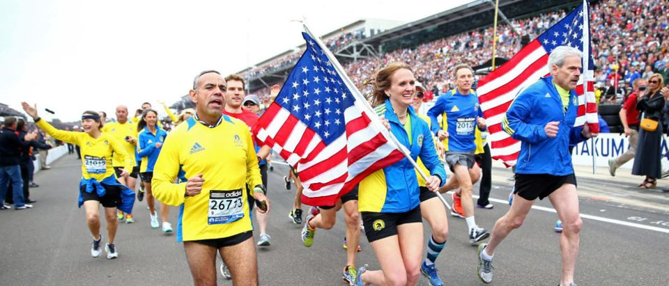 INDIANAPOLIS, IN - MAY 26: Runners who participated in the 2013 Boston Marathon run down pit road during the IZOD IndyCar Series 97th running of the Indianpolis 500 mile race at the Indianapolis Motor Speedway on May 26, 2013 in Indianapolis, Indiana. (Photo by Michael Hickey/Getty Images)