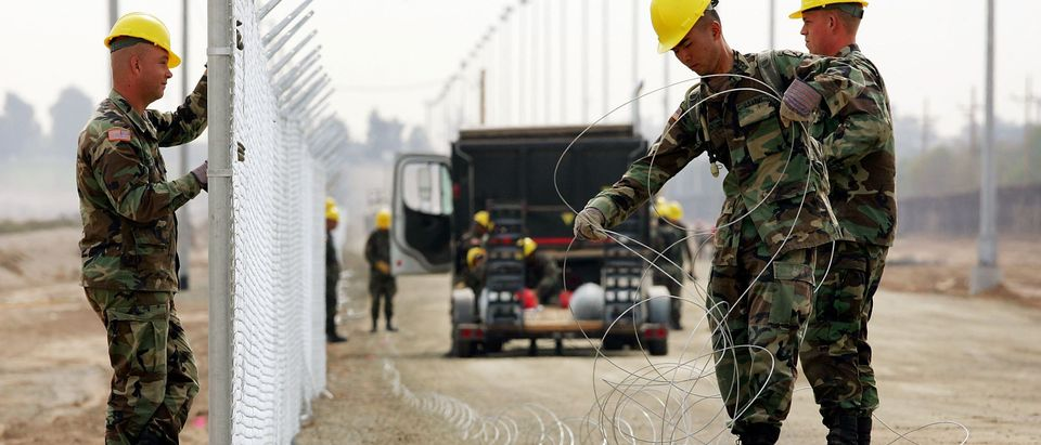 YUMA, AZ - MARCH 16: U.S. Army Rangers erect a chain-link fence that will be topped with barbed wire parallel to the primary steel U.S./Mexico border fence (R) to further fortify the border against people crossing illegally into the U.S. from Mexico on March 16, 2006 near the border town of near San Luis, south of Yuma, Arizona.
