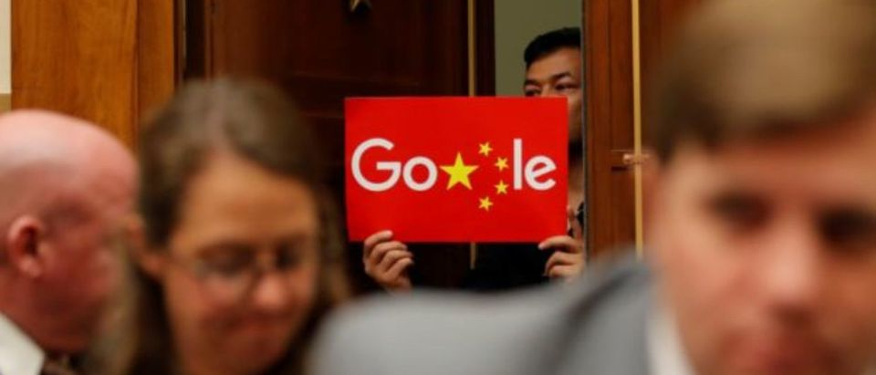 A demonstrator holds up a sign in the doorway as Google CEO Sundar Pichai testifies at a House Judiciary Committee on greater transparency in Washington, U.S., Dec. 11, 2018. REUTERS/Jim Young