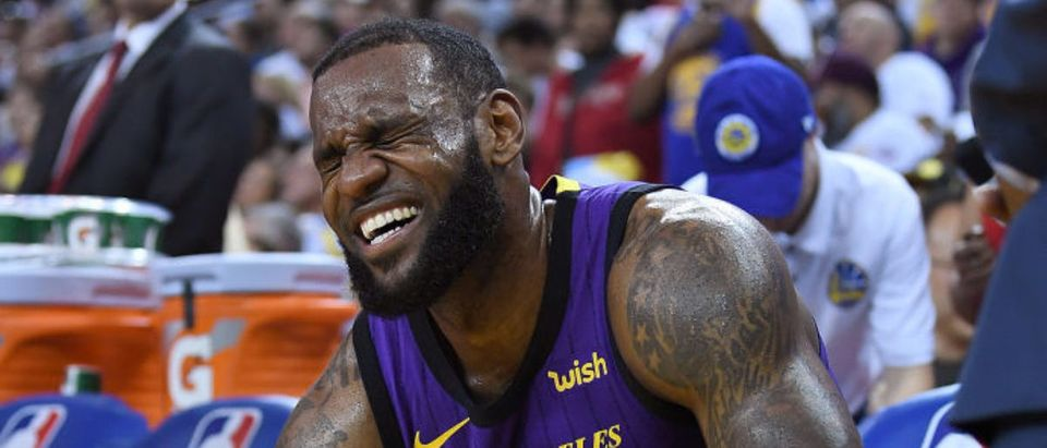 OAKLAND, CA - DECEMBER 25: LeBron James #23 of the Los Angeles Lakers crouches down in pain on the bench after he was hurt against the Golden State Warriors during the second half of their NBA Basketball game at ORACLE Arena on December 25, 2018 in Oakland, California. (Photo by Thearon W. Henderson/Getty Images)