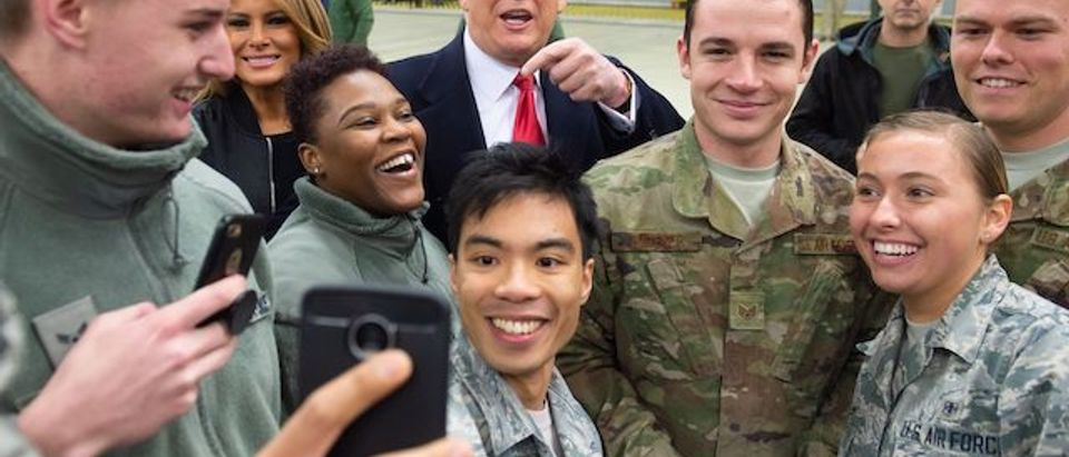"""US President Donald Trump and First Lady Melania Trump greet members of the US military during a stop at Ramstein Air Base in Germany, on December 27, 2018. - President Donald Trump used a lightning visit to Iraq -- his first with US troops in a conflict zone since being elected -- to defend the withdrawal from Syria and to declare an end to America's role as the global """"policeman."""" (Photo credit:SAUL LOEB/AFP/Getty Images)"""