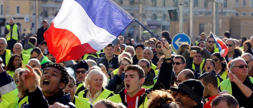 People wearing yellow vests, a symbol of a French drivers' protest against higher diesel fuel prices, wave French flags as they demonstrate in Marseille