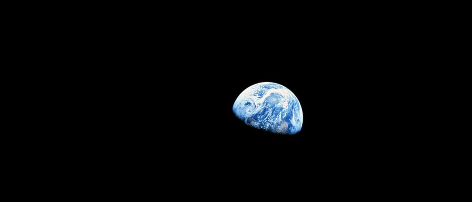 NASA handout image shows the distant blue Earth above the Moon's limb