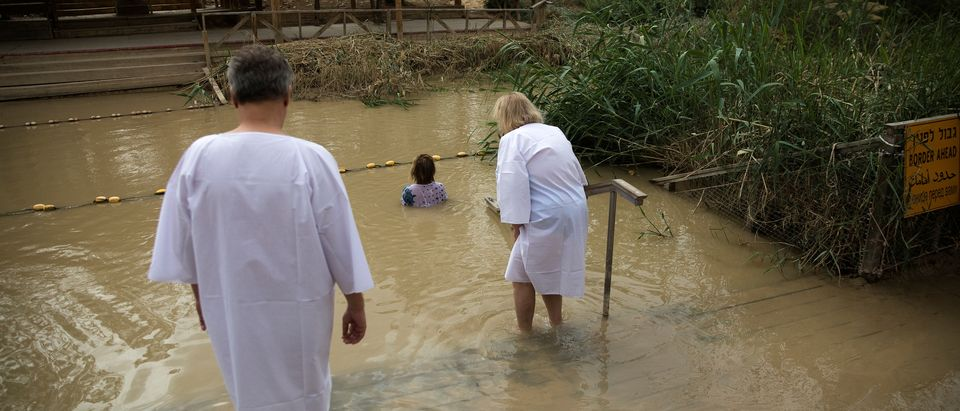 Christian pilgrims dip in the waters of the Jordan River at the baptism site known as Qasr al-Yahud, near Jericho