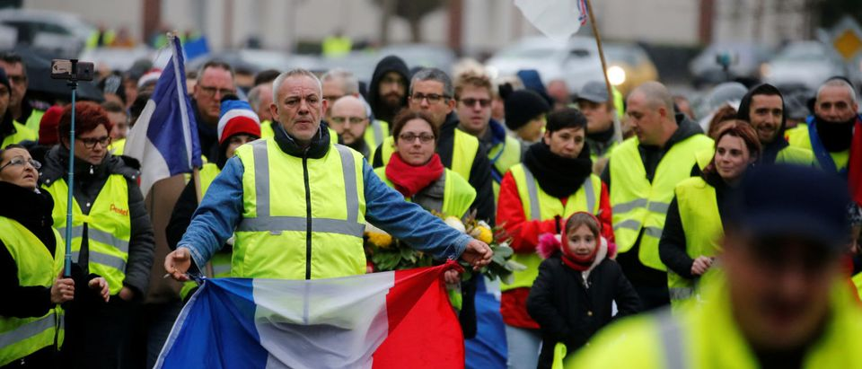 "A protester wearing a yellow vest holds a French flag during a demonstration by the ""yellow vests"" movement in Somain"
