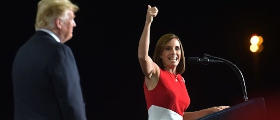 Representative Martha McSally speaks as US President Donald Trump looks on during a 'Make America Great' rally in Mesa, Arizona on October 19, 2018