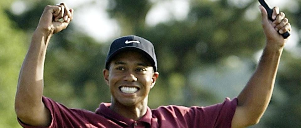 Tiger Woods of the US celebrates on the 18th hole 14 April 2002, after winning the 2002 Masters golf tournament at the Augusta National Golf Club in Augusta, GA. Woods finished the round one under par for a four day total of 12 under par . (Photo credit: ROBERT SULLIVAN/AFP/Getty Images)