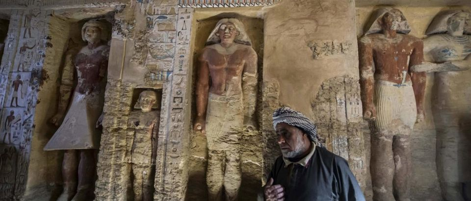 """Said Abdel Aal, an Egyptian archaelogical labourer, stands in a newly-discovered tomb at the Saqqara necropolis, 30 kilometres south of the Egyptian capital Cairo, on December 15, 2018, belonging to the high priest """"Wahtye"""" who served during the fifth dynasty reign of King Neferirkare (between 2500-2300 BC). - The well-preserved tomb is decorated with scenes showing the royal priest alongside his mother, wife and other members of his family, the ministry said in a statement. (KHALED DESOUKI/AFP/Getty Images)"""