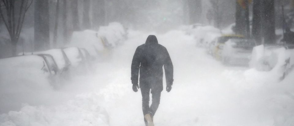 A man walks along a street covered by snow during a winter storm in Washington January 23, 2016. A winter storm dumped nearly 2 feet (58 cm) of snow on the suburbs of Washington, D.C., on Saturday before moving on to Philadelphia and New York, paralyzing road, rail and airline travel along the U.S. East Coast. REUTERS/Carlos Barria