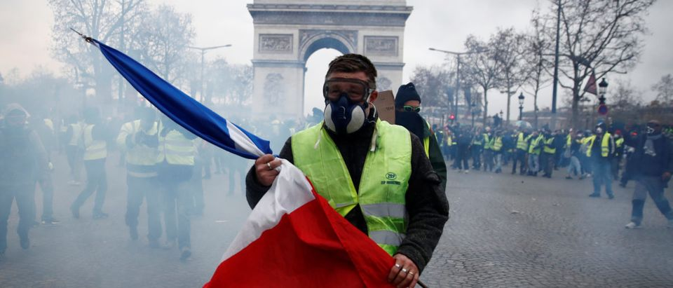"""A protester wearing a yellow vest holds a French flag as he walks among tear gas on the Champs-Elysees Avenue near the Arc de Triomphe during a national day of protest by the """"yellow vests"""" movement in Paris, France, December 8, 2018. REUTERS/Christian Hartmann"""