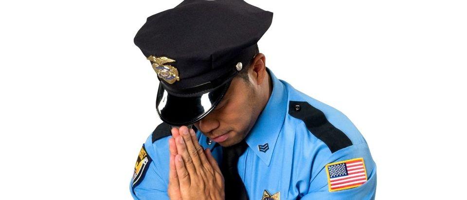 A police officer prays. Shutterstock image via user Lifetime Stock
