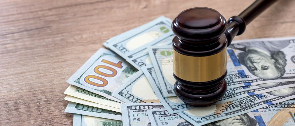 Wooden gavel with U.S. dollars on desk/ Shutterstock/ RomanR