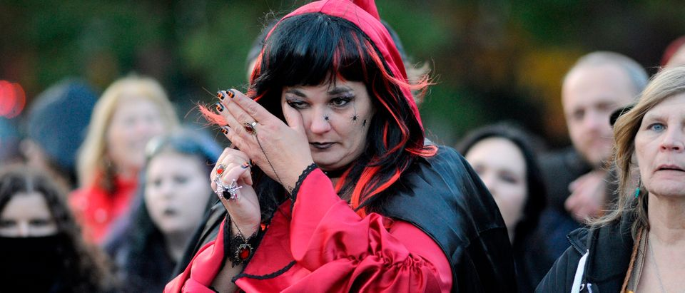 A witch cries during the Salem Witches' Magic Circle at Salem Common on Halloween in Salem, MA on October 31, 2018. - The ceremony involving local and visiting witches celebrates loved ones that have crossed over into the spirit world. The witches believe that on Halloween the veil between the living and the dead is at its thinnest and connections can be made to those being mourned or missed. JOSEPH PREZIOSO/AFP/Getty Images