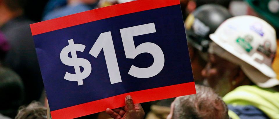 A supporter holds a sign aloft while listening to U.S. Democratic presidential candidate Hillary Clinton during a rally to celebrate the state of New York passing into law a $15 minimum wage in New York April 4, 2016. REUTERS/Lucas Jackson