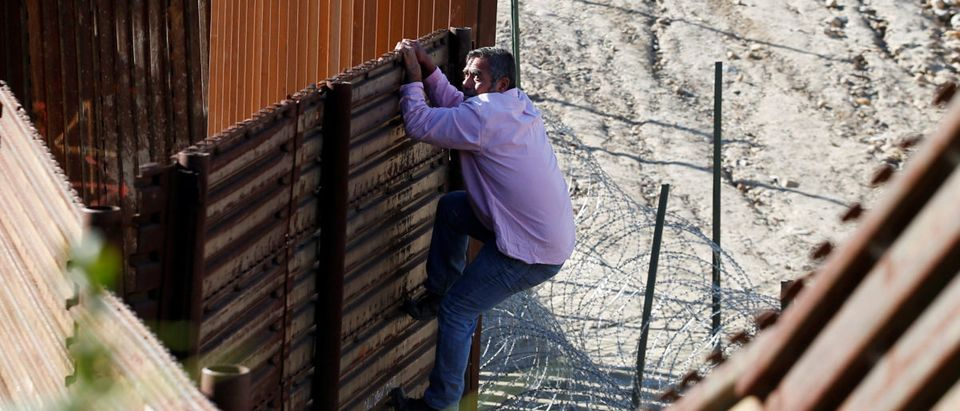 A migrant, who is trying to reach the United States, jumps the border fence to cross illegally from Mexico into the U.S., as pictured from Tijuana, Mexico, Dec. 28, 2018. REUTERS/Mohammed Salem