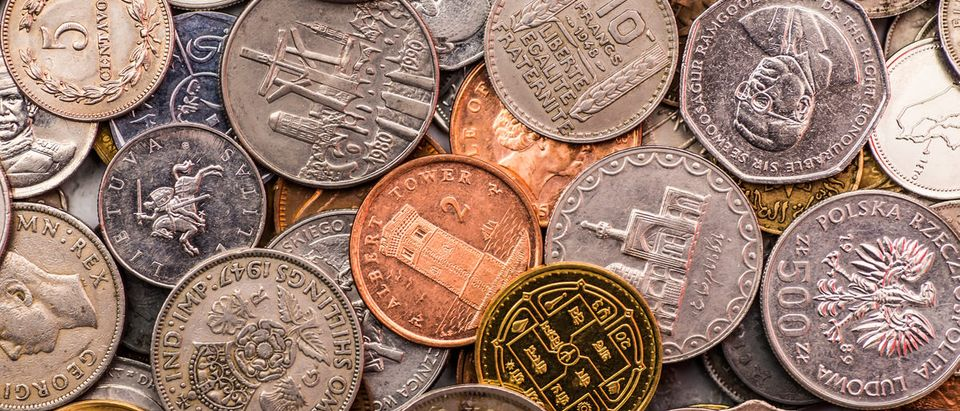 Coins of several currencies. (Shutterstock/Bukhta Yurii)
