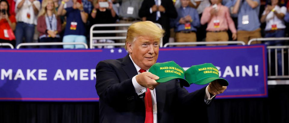 """U.S. President Donald Trump holds """"Make Our Farmers Great Again"""" hats during a """"Make America Great Again"""" rally in Evansville, Indiana, U.S., Aug. 30, 2018. REUTERS/Kevin Lamarque"""