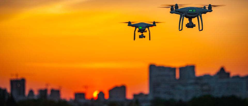 Drones fly above a city at night. (Shutterstock/Volodymyr Goinyk)