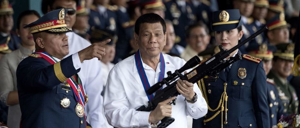 TOPSHOT - Philippine President Rodrigo Duterte holds a Galil sniper rifle with outgoing Philippine National Police (PNP) chief Ronald dela Rosa (L) during the change of command ceremony at Camp Crame in Manila on April 19, 2018. NOEL CELIS/AFP/Getty Images)