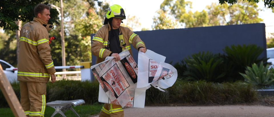 A fire fighter is seen carrying hazardous material bags into the South Korean consulate in Melbourne, Australia, January 9, 2019. Staff have been evacuated as emergency crews respond to a number of incidents involving foreign consulates in Melbourne. AAP Image/James Ross via REUTERS