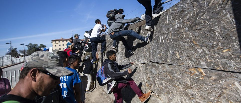 A group of Central American migrants -mostly from Honduras- get over a fence as they try to reach the US-Mexico border near the El Chaparral border crossing in Tijuana, Baja California State, Mexico, on Nov. 25, 2018./ PEDRO PARDO/AFP/Getty Images