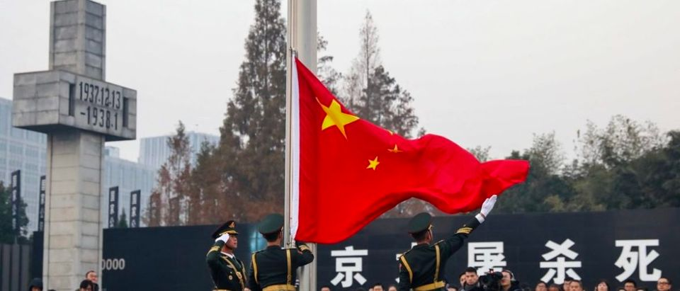 People's Liberation Army (PLA) soldiers raise the Chinese flag during a memorial ceremony at the Nanjing Massacre Memorial Hall on the annual national day of remembrance to commemorate the 81st anniversary of the massacre in Nanjing in China's eastern Jiangsu province on December 13, 2018. (Photo by STR / AFP) / China OUT (Photo credit should read STR/AFP/Getty Images)