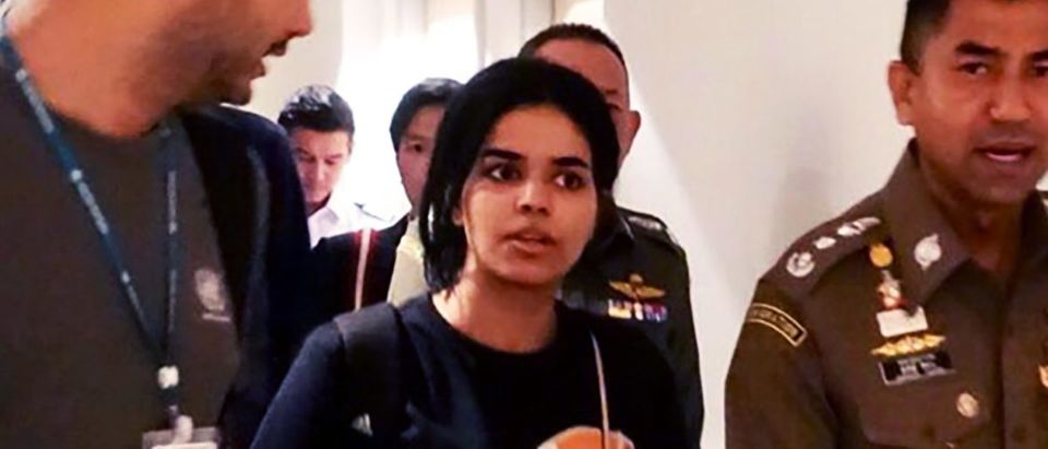 This handout picture taken and released by Thai Immigration Bureau on January 7, 2019 shows 18-year-old Saudi woman Rahaf Mohammed al-Qanun (2nd-L) is being escorted by the Thai immigration officer and United Nations High Commissioner for Refugees (UNHCR) officials at the Suvarnabhumi international airport in Bangkok. (AFP/Getty Images)