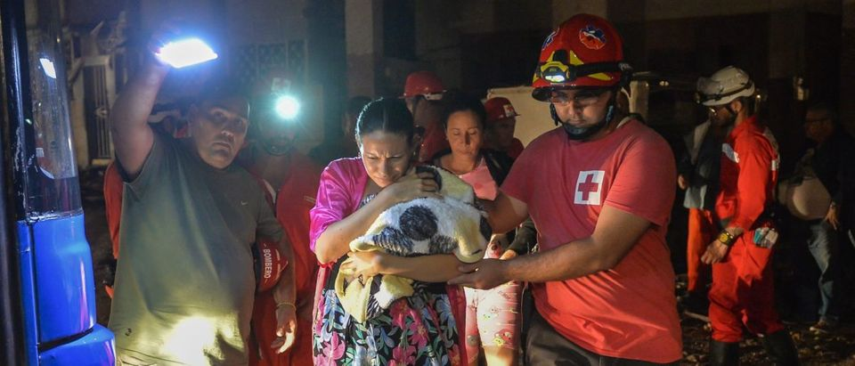 Cuban firefighters assist the evacuation of a mother and her baby in the tornado-hit Luyano neighborhood in Havana early on January 28, 2019. (YAMIL LAGE/AFP/Getty Images)