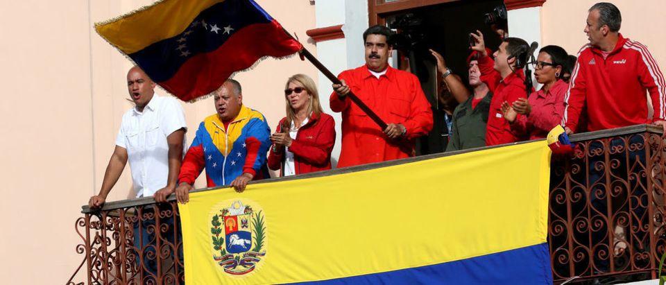 President of Venezuela Nicolás Maduro waves a national flag