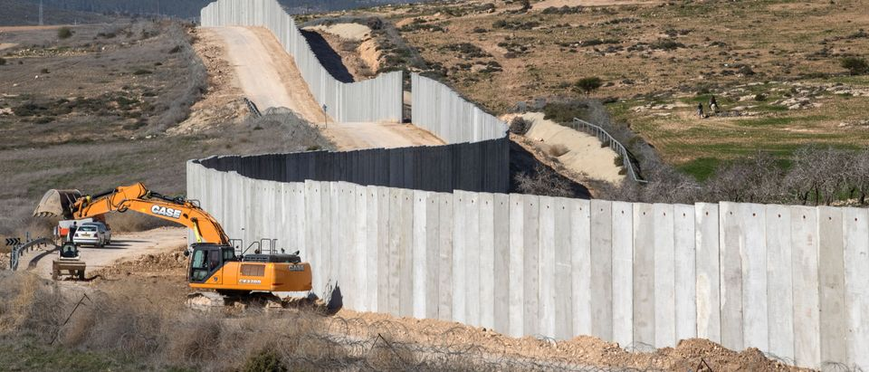 A picture taken near the southern kibbutz of Lahav on February 7, 2017, shows workers building a new section of the controversial Israeli separation wall dividing Israel from the West Bank. (JACK GUEZ/AFP/Getty Images)