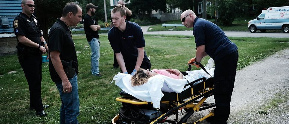 Medical workers and police treat a woman who has overdosed on heroin, the second case in a matter of minutes, on July 14, 2017 in Warren, Ohio. According to recent statistics, at least 4,149 Ohioans died from drug overdoses in 2016, a 36 percent leap from just the previous year and making Ohio the leader in the nation's overdose deaths. (Photo by Spencer Platt/Getty Images)