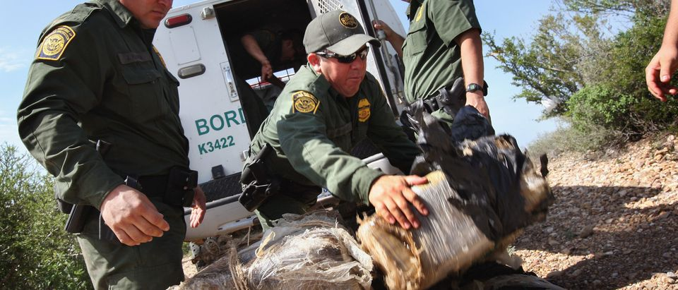 U.S. Border Patrol agents stack more than 400 pounds of marijuana seized from drug smugglers after it was brought across the Rio Grande River from Mexico into the United States August 7, 2008 near Laredo, Texas. (Photo by John Moore/Getty Images)