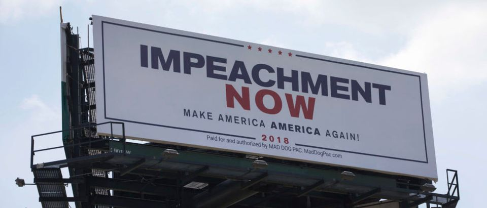"A billboard reading: ""Impeachment Now Make America America Again!"" calling for President Donald Trump's impeachment is seen along a street leading to Mar-A-Lago on March 19, 2018 in West Palm Beach, Florida. (Photo by Joe Raedle/Getty Images)"