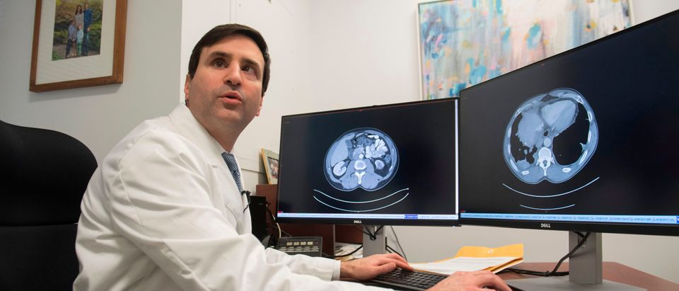 Dr. Christian Hinrichs, an investigator at the National Cancer Institute, shows a patient's CT scans, one with visible cancer (R) and the other showing a clean scan after treatment (L), as he speaks about his research in immunotherapy for HPV+ cancers, in his lab at the National Institutes of Health (NIH) in Bethesda, Maryland, February 7, 2018. (SAUL LOEB/AFP/Getty Images)